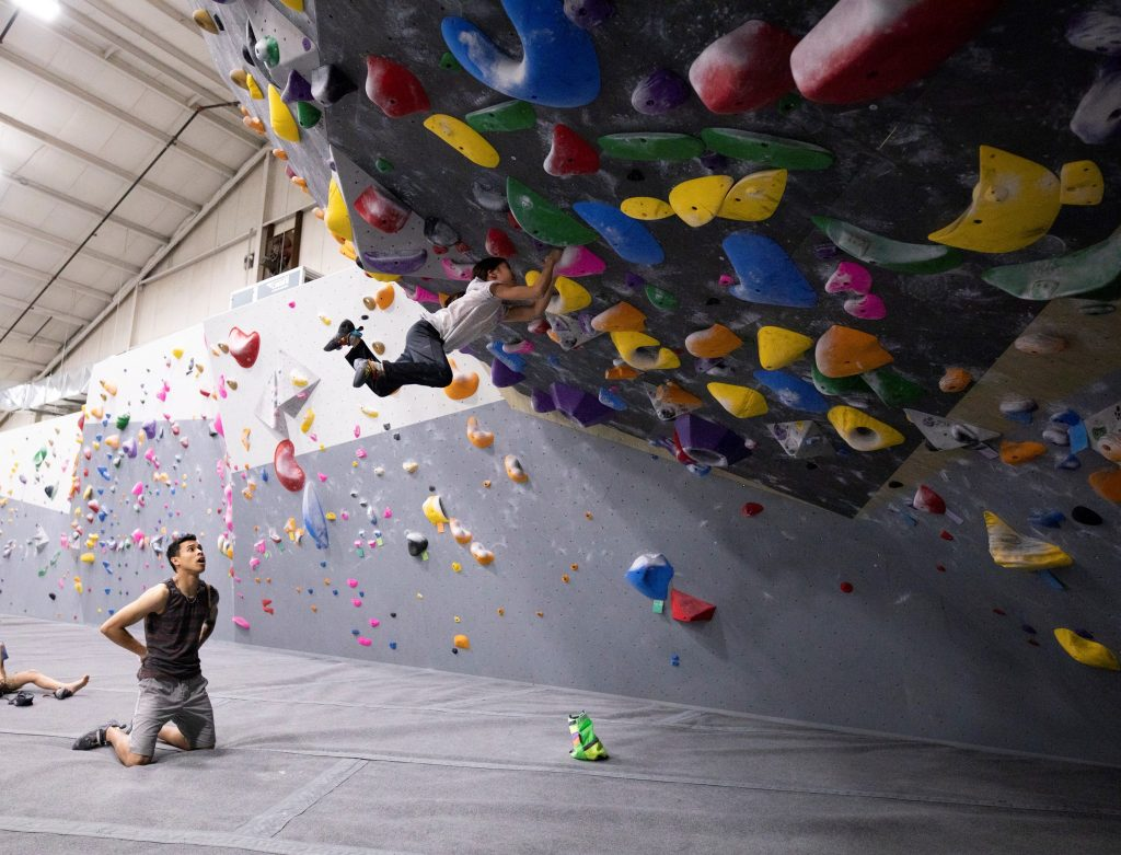 man watching young man bouldering, difficult problem